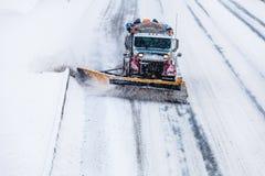 取消雪的除雪机从高速公路在暴风雪期间 免版税图库摄影