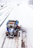 取消雪的除雪机从高速公路在暴风雪期间 免版税库存照片