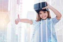 取消VR耳机和显示的微笑的小女孩赞许 免版税库存图片