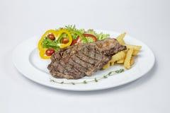 取笑眼睛牛排供食用新鲜的油煎的沙拉和法语 库存照片