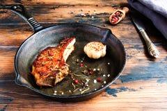 取笑眼睛猪肉牛排和被烘烤的大蒜在黑铸铁长柄浅锅在木土气桌上 胡椒和葡萄酒刀子 免版税库存照片