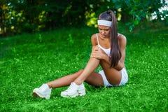 受伤的女运动员坐草 库存图片