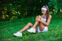 受伤的女运动员坐草 库存照片