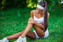 受伤的女运动员坐草 图库摄影