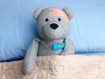 受伤的玩具熊涂灰泥顶头床温度计流感 图库摄影