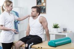 受伤的运动员和年轻生理治疗师 图库摄影