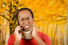 受伤的年轻正面黑西班牙男性佩带的护颈垫,谈话在电话和手在极度痛苦的藏品支持 免版税库存照片