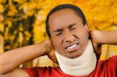 受伤的黑西班牙男性佩带的护颈垫,在痛苦中握手在做面孔的支持附近极度痛苦,黄色 免版税库存照片