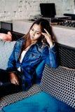 变冷在俱乐部的蓝色牛仔裤的华美的少妇 图库摄影