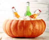 变冷在南瓜冰桶的被装瓶的饮料 免版税库存图片