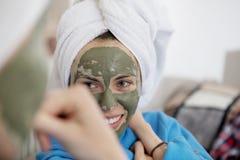 变冷在卧室和做黏土脸面护理面具的妈妈和她的女儿 库存图片