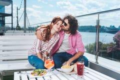变冷在大阳台的年轻时髦的夫妇有河视图 免版税库存图片