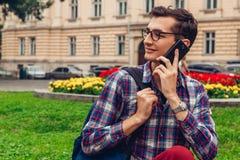 变冷在春天校园公园的英俊的专业生 愉快的人学生坐草和谈话在电话 免版税图库摄影