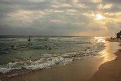 变冷并且放松在斯里兰卡的海岛上的日落期间、地方渔夫和美丽的干净的海滩和波浪 免版税图库摄影