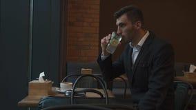 变冷静的白色衬衣和无尾礼服饮用的柠檬水的年轻英俊的人在一个热的夏日 影视素材