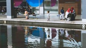 变化在英国,使用在与他们的同水准的水附近的孩子 免版税图库摄影