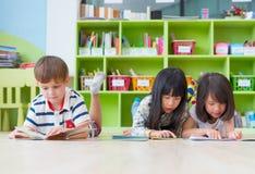 变化孩子在地板和读书在prescho的传说书放下 免版税库存照片