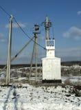 变压器分站电源配电所在村庄和蓝天的背景的冬天 免版税库存图片