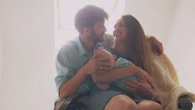 变安静她的一个摇椅父亲轻拍的美丽的愉快的家庭母亲婴孩在他的儿子和亲吻妻子头  4K 免版税库存图片