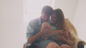 变安静她的一个摇椅父亲轻拍的美丽的愉快的家庭母亲婴孩在他的儿子和亲吻妻子头  4K 免版税库存照片