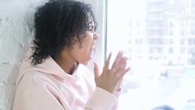 变年轻非洲的妇女尖叫和疯狂,坐在窗口 股票视频
