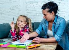 变得的母亲沮丧与女儿,做家庭作业在家坐沙发在学习困难家庭作业育儿 免版税图库摄影