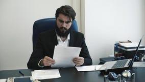 变得确信的商人的人看通过纸和恼怒在办公室 重点在工作 股票录像
