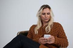变性使用手机,当坐椅子时 库存照片