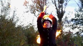 变戏法者在慢动作的一个森林里转动两个火球在他的头上的 股票视频