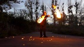 变戏法者转动两个火球靠近土地在晚上在Slo Mo 股票视频