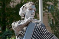 变成银色有作为二战的俄国苏联士兵穿戴的手风琴的被绘的艺术家在城市街道上的 库存照片