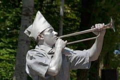 变成银色有作为在城市街道上的苏联先驱穿戴的垫铁喇叭的被绘的艺术家 库存照片