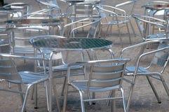 变成银色色的alluminium桌和椅子在咖啡馆之外 免版税库存图片
