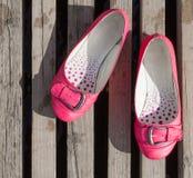 变粉红色在一个被装饰的木地板上的使用的鞋子 库存图片