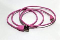 变粉红色有缆绳的使用的USB插座在白色背景 免版税库存照片