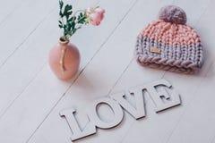 变粉红色说谎在白色木地板上的被编织的帽子 库存图片