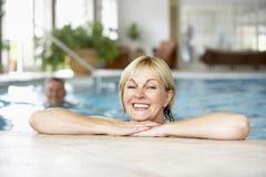 变老的夫妇中间池游泳 库存图片