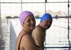 变老的夫妇中间池游泳 免版税库存图片