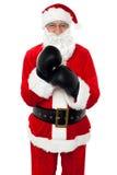 变老的快乐的圣诞老人佩带的拳击手套 库存图片