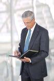 变老的生意人中间笔记本文字 免版税库存照片