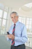 变老的生意人中间texting 免版税库存照片