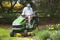 变老的草坪人中间刈草机骑马 免版税库存照片