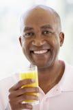 变老的饮用的新鲜的汁液人中间桔子 免版税库存图片