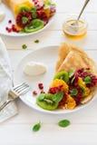 变薄有新鲜的猕猴桃、桔子,西西里人的桔子,蜂蜜,奶油色和薄荷叶的绉纱 库存图片