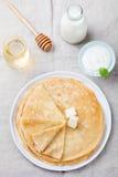 变薄绉纱或薄煎饼用黄油、蜂蜜和酸性稀奶油在一张土气纺织品背景顶视图 库存照片