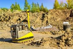 变紧密的土壤的手工猛撞的机器在路 库存照片