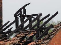 变黑的屋顶椽木被烧在居民住房下在火以后 库存照片