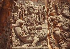 叙述印度的战争之神, Murugan,在印地安寺庙门面与带状装饰从印度文本的传奇 Halebidu,印度 免版税库存照片