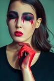 离经叛道之人的妖怪画象有混乱肮脏的色的构成的在她的面孔 有红色血淋淋的泪花和手的哭泣的妇女 万圣夜conce 库存图片