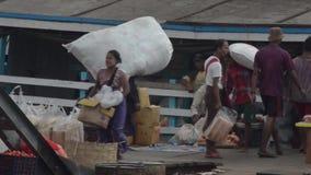 口岸、奎伊&跳船:亚洲-搬运工运载在小船上的巨型的大袋 影视素材